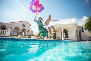 Happy young couple jumping into the pool while holding a bunch of balloons